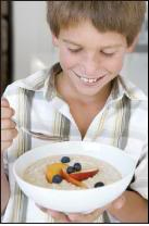 Boy holding bowl of cereal